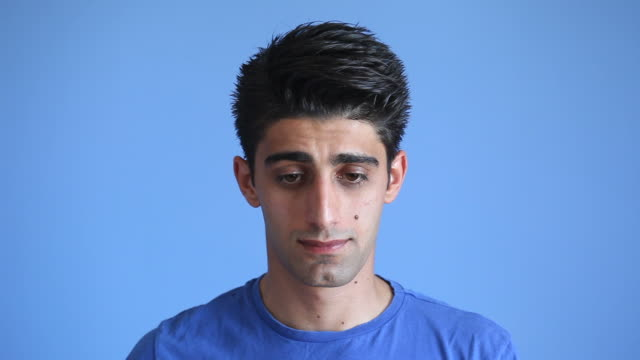 Facial Expression Of Shy Adult Man On Blue Background video