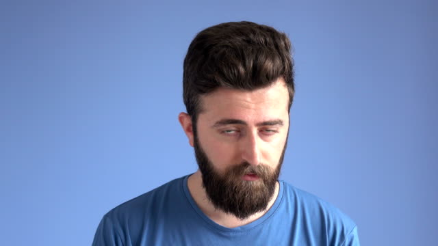 Facial Expression Of Shy Adult Man On Blue Background