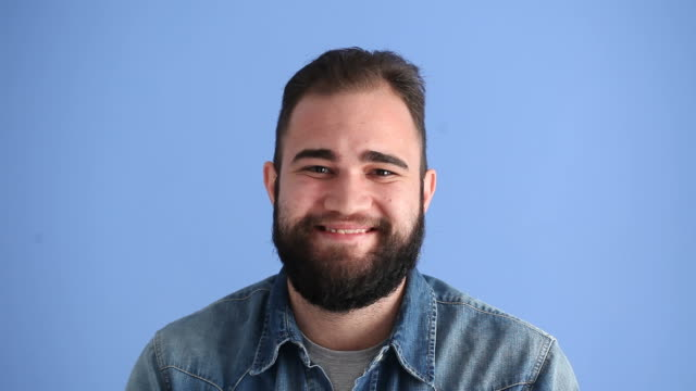 Facial Expression Of Smiling Adult Man On Blue Background HD video of facial expression of smiling adult man on blue background.The model is a young man in his 20's.He is wearing a blue shirt.He is making faces for positive surprise and shock.The video was shot with a full frame DSLR camera in studio. background color stock videos & royalty-free footage