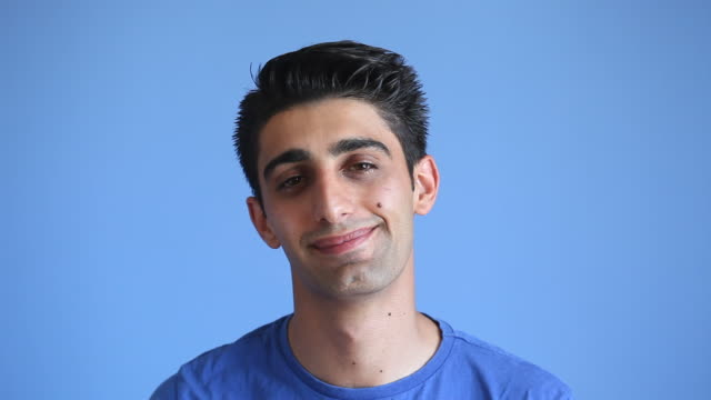 Facial Expression Of Smiling Adult Man On Blue Background video