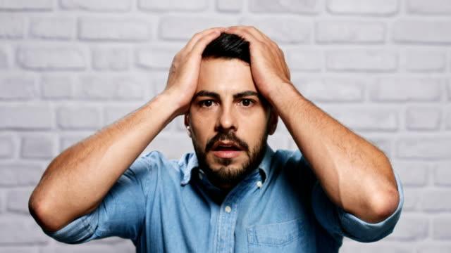 レンガの壁の若いひげ男の表情 - 身ぶり点の映像素材/bロール