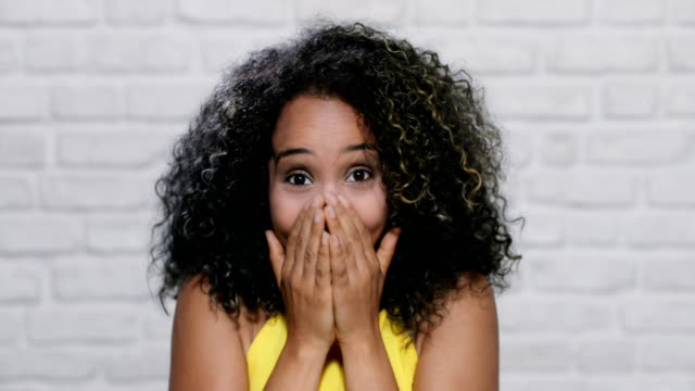 facial expressions of young black woman on brick wall - sorpresa video stock e b–roll