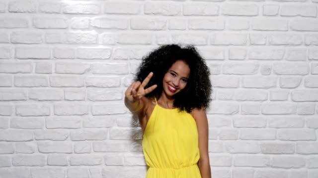 facial expressions of young black woman on brick wall - gestykulować filmów i materiałów b-roll