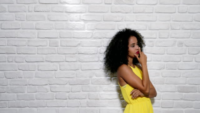 Facial Expressions Of Young Black Woman On Brick Wall Portrait of puzzled woman having doubts, doubtful black girl thinking. Copy space thinking stock videos & royalty-free footage