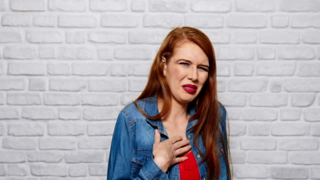 Facial Expressions Of Young Redhead Woman On Brick Wall Portrait of disgusted woman, hispanic redhead girl showing disgust for bad smell or taste. Copy space disgust stock videos & royalty-free footage