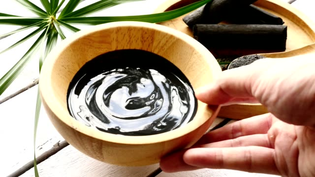 facial mask and scrub by activated charcoal powder and yogurt on wooden table - spa facial stock videos & royalty-free footage
