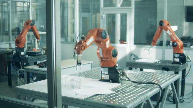 vidéos et rushes de une installation avec des dispositifs robotiques fonctionnant. - bras humain