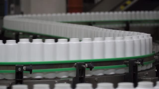 Factory and research concept. Clip. Bottles moving on manufacturing line. Bottles in line on conveyor belt. Production process video