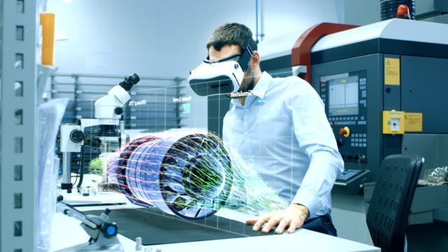 Video Factory Chief Engineer Wearing VR Headset Designs Engine Turbine on the Holographic Projection Table.  Futuristic Design of Virtual Mixed Reality Application.