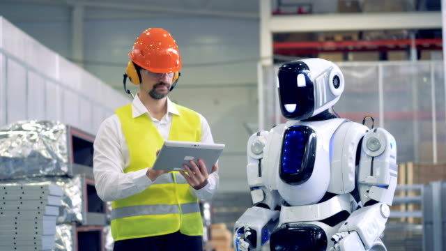 Factory employee is communicating with a humanoid in gestures Factory employee is communicating with a humanoid in gestures. 4K robot stock videos & royalty-free footage