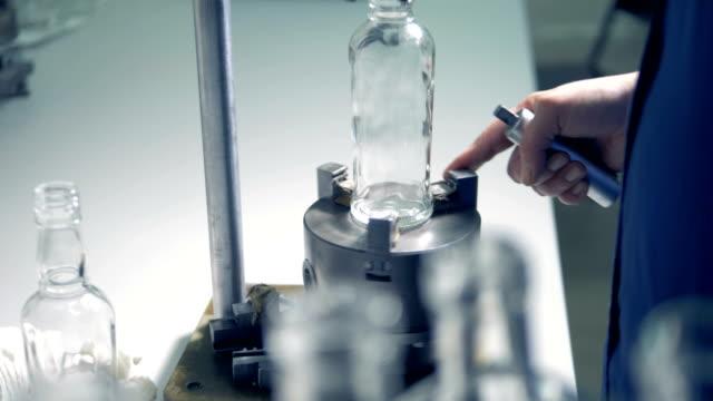 factory anställda roterar en glaskroppen flaska som placeras på en metall stativ - wine box bildbanksvideor och videomaterial från bakom kulisserna