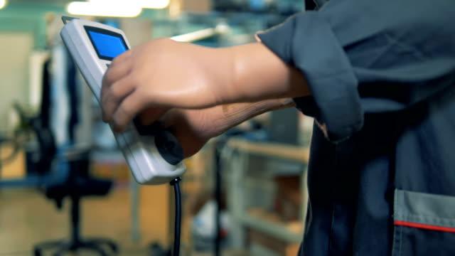 人工手で工場の従業員は、ボタンを押して、リモートコントロールを使用しています。 - 人里離れた点の映像素材/bロール