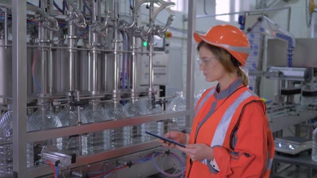 fabrik engineer hündin in helm verwendet digitale tablette, um die arbeit der gürtellinie für die abfüllung von wasser in flaschen in der anlage zu kontrollieren - new work stock-videos und b-roll-filmmaterial