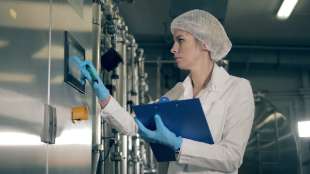 Factory equipment and a female factory expert recording its data Factory equipment and a female expert recording its data. 4K manufacturing occupation stock videos & royalty-free footage