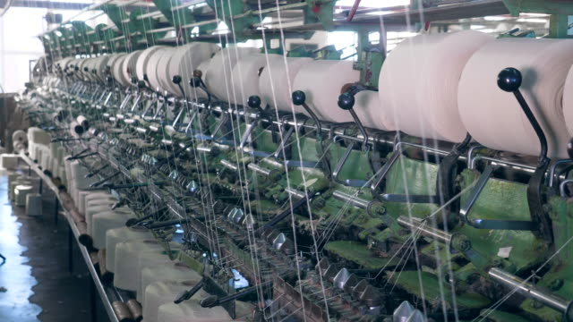 factory equipment works with clews, spooling threads automatically. - cilindro video stock e b–roll