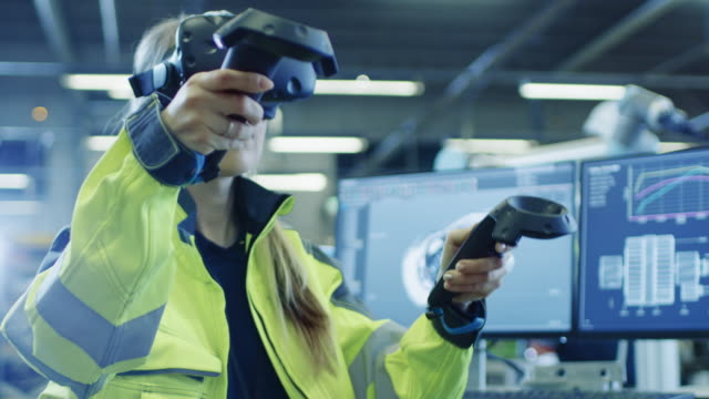 factory: female industrial engineer wearing virtual reality headset and holding controllers, she uses vr technology for industrial design, development and prototyping in cad software. - деятельность стоковые видео и кадры b-roll