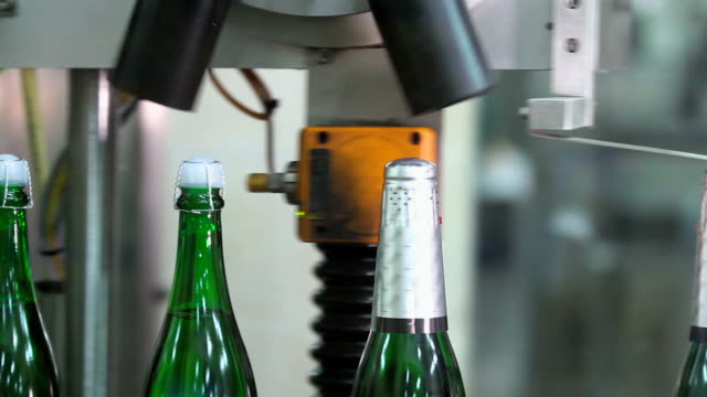 Factory for the production of champagne. Sealing of champagne with a stopper at a factory of sparkling wines.Wrapping aluminum foil bottle neck with champagne. Bottles with champagne are moving along the conveyor belt. Ambient sound at clip. cork stopper stock videos & royalty-free footage