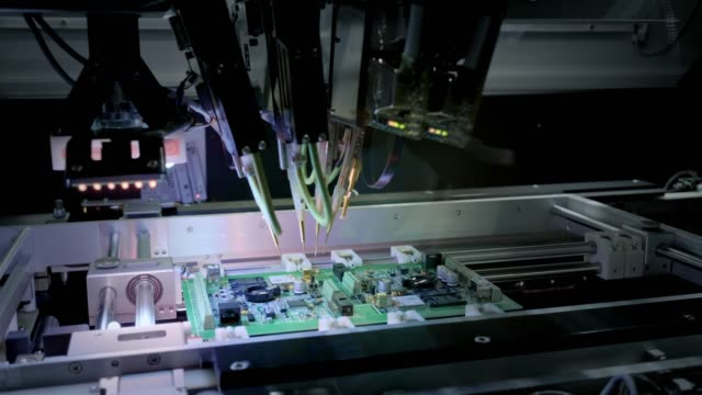factory machine at work: printed circuit board being assembled with automated robotic arm, surface mounted technology connecting microchips to the motherboard. time lapse macro close-up footage. - przemysł elektroniczny filmów i materiałów b-roll