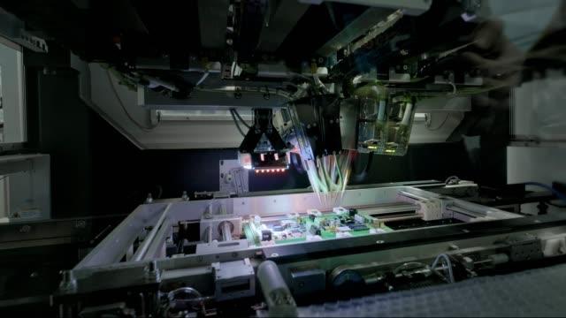工場出荷時の機械:自動ロボットアームで組み立てられるプリント回路基板、マイクロチップをマザーボードに接続する表面実装技術。タイムラプスマクロクローズアップ映像。 - 半導体点の映像素材/bロール