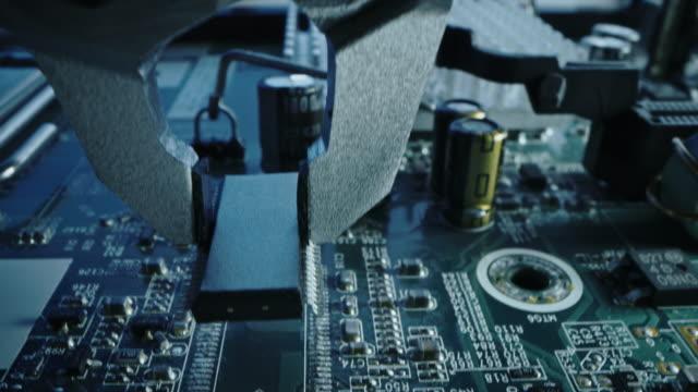 職場の工場機械:ロボットアームで組み立てられるプリント回路基板、マイクロチップを接続する表面実装技術、cpuプロセッサをマザーボードに接続します。フォーカス マクロのクローズア� - 半導体点の映像素材/bロール