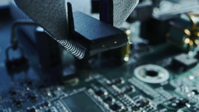 vídeos de stock, filmes e b-roll de máquina de fábrica no trabalho: placa de circuito impressa que está sendo montada com braço robótico, tecnologia montada em superfície conectando microchips, processador de cpu à placa-mãe. concentrando macro close-up - automatizado