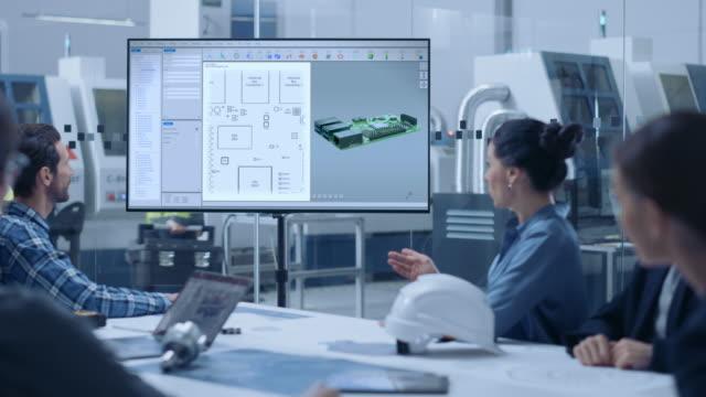 vídeos y material grabado en eventos de stock de sala de reuniones de la oficina de fábrica: equipo diverso de ingenieros de diseño de computadoras, gerentes e inversores hablando en la mesa de conferencias, viendo la televisión interactiva que muestra el modelo conceptual 3d de la placa de circuito i - placa madre