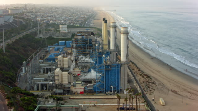 aerial factory on the sandy beach in california, usa - centrale elettrica video stock e b–roll