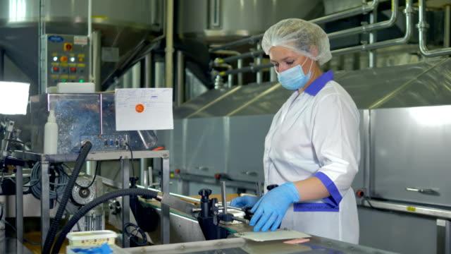a fabrika operatör bir plastik kap ve maske içinde peynir paketleri denetler. 4k. - maske stok videoları ve detay görüntü çekimi