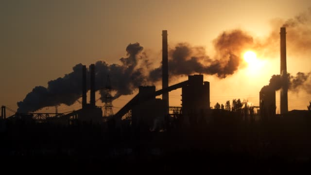 factory pipe polluting air at sunrise. - clima video stock e b–roll