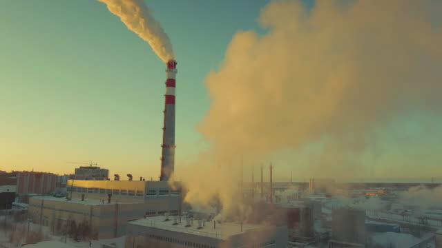 Factory pipe throws a lot of smog. Smoke looks beautiful but dangerous at sunset