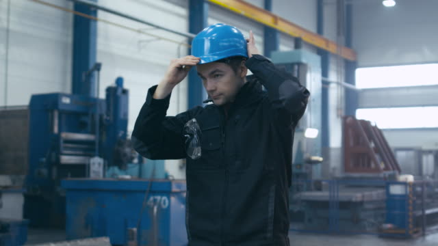 Factory worker in blue uniform is putting his hard hat and goggles on while walking.