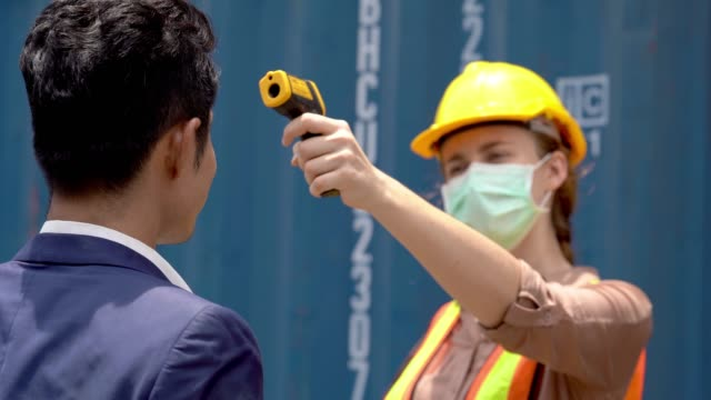 factory worker in mask face and using measures temperature check body temperature at workplaces with a thermometer during a virus pandemic. And man worker going pass inside factory.