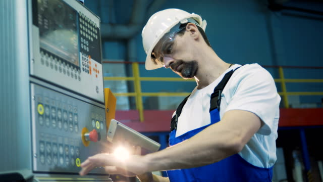 stockvideo's en b-roll-footage met factory worker beheert een control board - raffinaderij