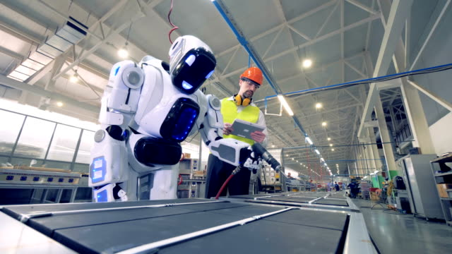 factory worker is regulating robot's settings by remote control during working process - rivoluzione industriale video stock e b–roll