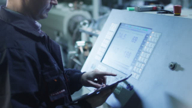 fabrika işçisi fabrikada cnc torna makinesi kurma - i̇malat ekipmanları stok videoları ve detay görüntü çekimi