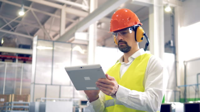 factory worker is standing and working with his tablet at a factory warehouse. - occhiata laterale video stock e b–roll