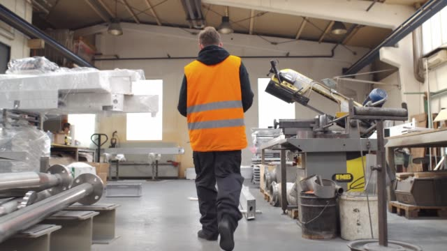 factory worker is walking through industrial facilities (shot from behind) - attrezzatura industriale video stock e b–roll