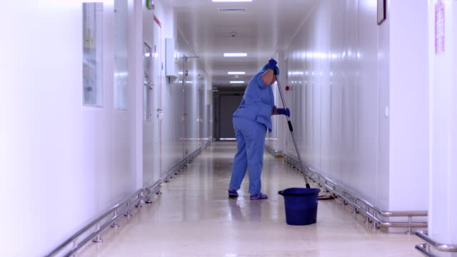 Factory worker mopping floor in hospital corridor. Cleaner cleaning corridor