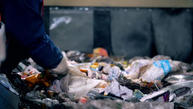 工場労働者は、ライン上のゴミをソートし、クローズアップします。作業者は、ゴミでいっぱいの移動線に用紙を並べ替えます。 - 服装点の映像素材/bロール