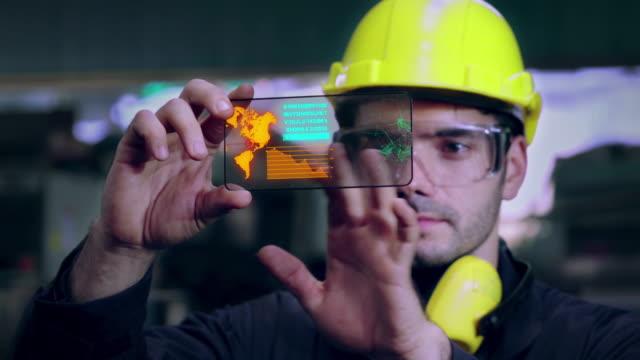 fabriksarbetare använda framtida holografisk skärm enhet för att styra tillverkningen - datorstödd tillverkning bildbanksvideor och videomaterial från bakom kulisserna
