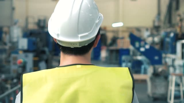 Factory worker with safety hard hat walking through industrial facilities