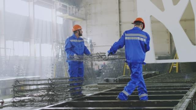 vídeos y material grabado en eventos de stock de trabajadores de fábricas que traen armaduras en la fabricación - brigada
