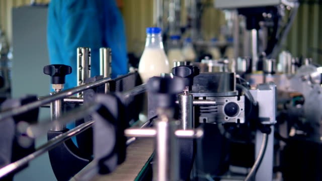 Factory workers receive rotating milk bottles for delivery. video