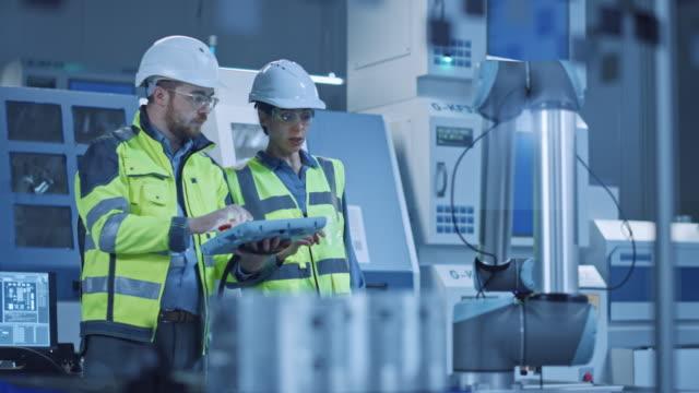fabrika atölyesi: profesyonel kadın mühendis, erkek makine operatörü üretim hattı için endüstriyel dijital tablet bilgisayar kullanımı ve program robot kolu. cnc makineleri ile yüksek teknoloji tesisi - plant stem stok videoları ve detay görüntü çekimi