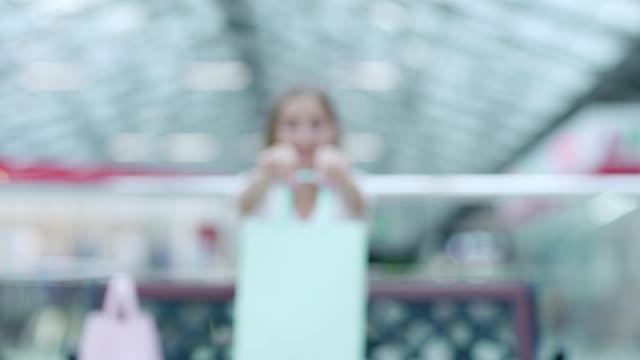 tona in av vacker och glad kvinna visar ljus mint shoppingväska med inköp efter lyckad shopping i gallerian - intoning bildbanksvideor och videomaterial från bakom kulisserna