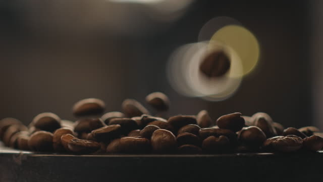 Fade in shot of roasted coffee beans at factory