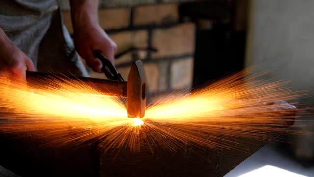 vista fiabesca di un uomo in uniforme che colpisce un'asta metallica fusa con un martello su un'incudine d'acciaio in una tradizionale officina fabbro. - fabbro ferraio video stock e b–roll