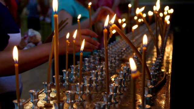 getreue personen beleuchtung kerzen in der kirche gebet nahaufnahme - mahnwachen stock-videos und b-roll-filmmaterial