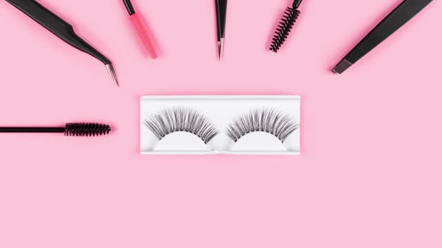 Fake eyelashes. Tools for eye lash extensions on trendy pastel pink background. Concept. Eyelash curler, tweezers, brushes. Makeup accessories. Cosmetic products. Top view. Stop motion. Beauty pattern Fake eyelashes. Tools for eye lash extensions on trendy pastel pink background. Concept. Eyelash curler, tweezers, brushes. Makeup accessories. Cosmetic products. Top view. Stop motion. Beauty pattern eyelash stock videos & royalty-free footage