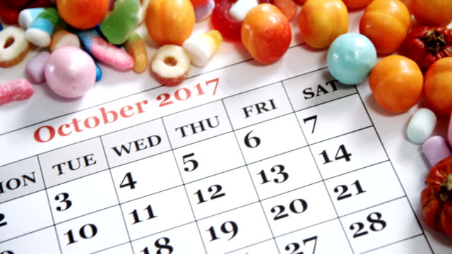 Fake spider on a calendar with various sweet foods 4k video